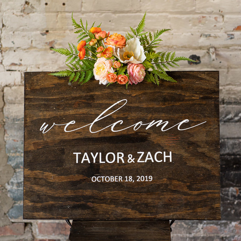 A wood sign with an orange and pink floral swag.