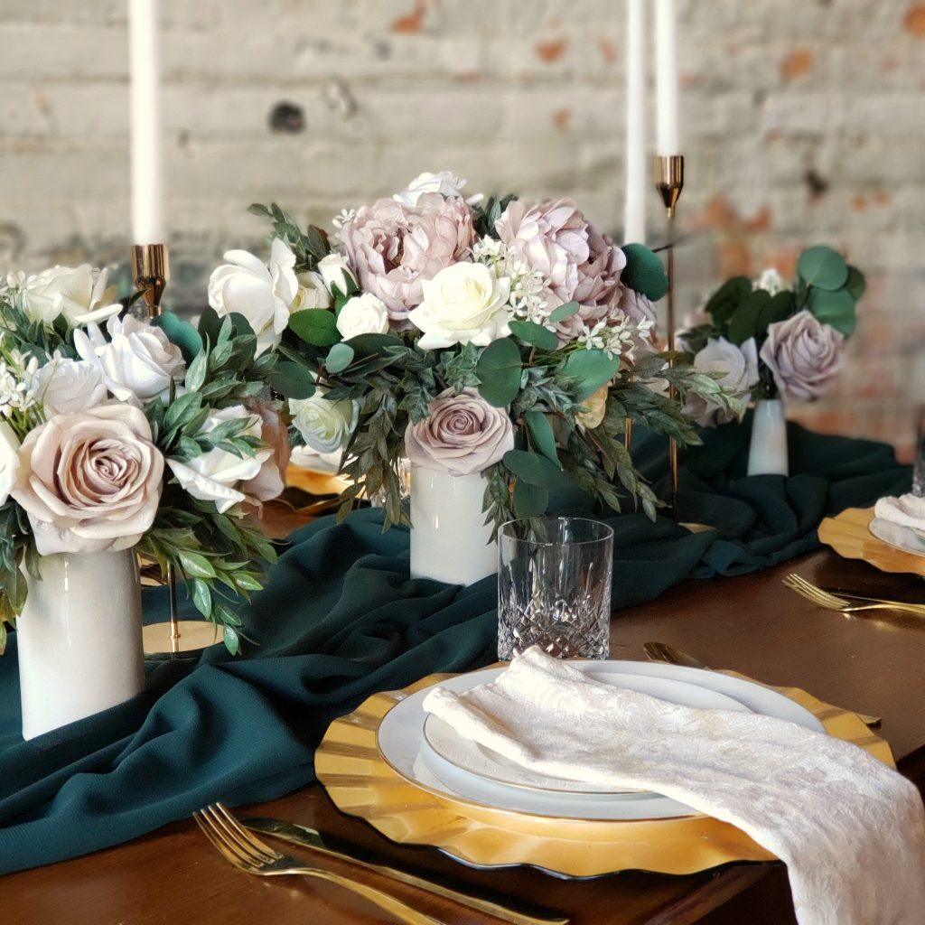 A tablesetting with mauve peony centerpieces and white taper candles.